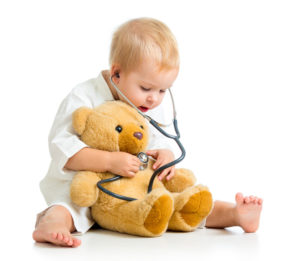 Child with stethoscope listening to stuffed bear's heart
