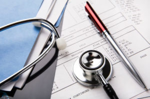 medical record, pen, and stethoscope