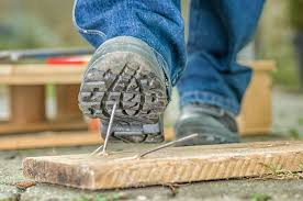 Man;s booted foot stepping on a nail